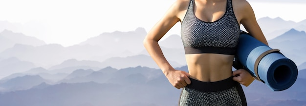 Молодая стройная спортивная девушка в спортивной одежде выполняет комплекс упражнений на фоне гор