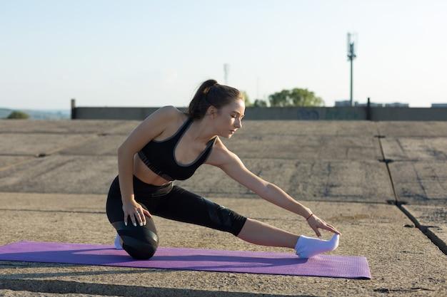 Молодая стройная спортивная девушка в спортивной одежде выполняет комплекс упражнений.