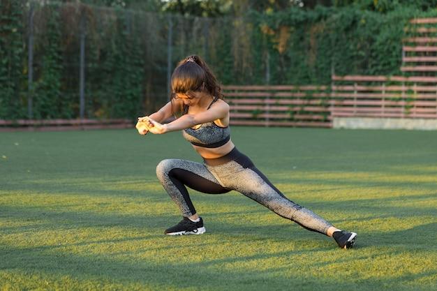 Молодая стройная спортивная девушка в спортивной одежде со змеиным принтом выполняет комплекс упражнений. фитнес и здоровый образ жизни.
