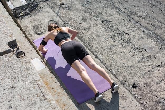 スネークスキンのプリントが施されたスポーツウェアの若いスリムなアスレチックガールが一連のエクササイズを行います