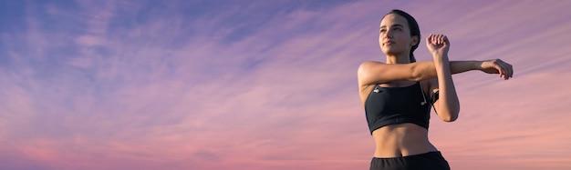 Молодая стройная спортивная девушка в спортивной одежде со змеиным принтом выполняет комплекс упражнений