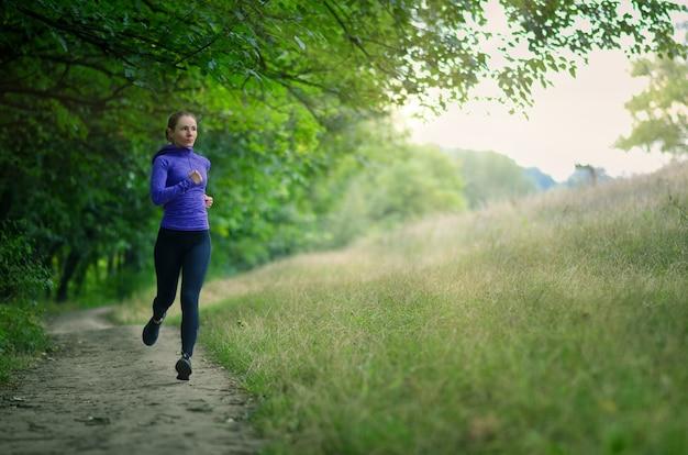 검은 색 스포츠 레깅스와 파란색 재킷을 입은 젊은 슬림 러너가 아름다운 녹색 숲의 길을 따라 달려갑니다. 사진은 활동적인 건강한 라이프 스타일을 보여줍니다.