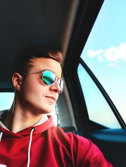 젊은 미소를 지은 남자가 공항으로가는 택시의 뒷좌석에 앉아 셀카를 찍고 있습니다.