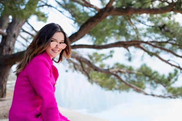 若い、笑顔の美しい少女は、海の美しい景色を楽しんでいます。ハッピーは桟橋の端に座って山々を見ています。自然と二人きり。