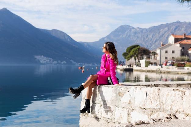 Молодая, улыбающаяся красивая девушка наслаждается прекрасным видом на море. хэппи сидит на краю пристани и смотрит на горы. наедине с природой.