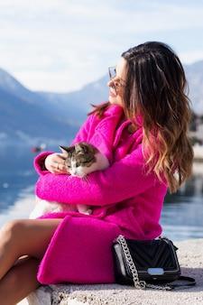 Молодая, улыбающаяся красивая девушка наслаждается прекрасным видом на море. хэппи сидит на краю причала с кошкой на руках. наедине с природой.