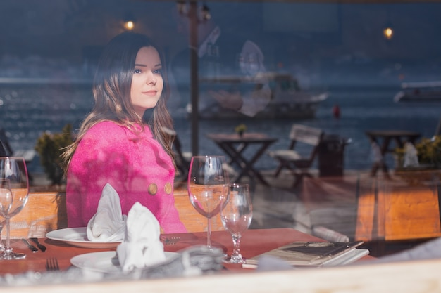 젊고 웃는 아름다운 소녀는 바다의 아름다운 전망을 즐깁니다. 카페에 앉아 아름다운 경치를 바라보고 있습니다.