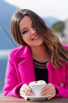 젊고 웃는 아름다운 소녀는 바다의 아름다운 전망을 즐깁니다. 길거리 카페에 앉아 커피를 마신다. 자연과 함께.