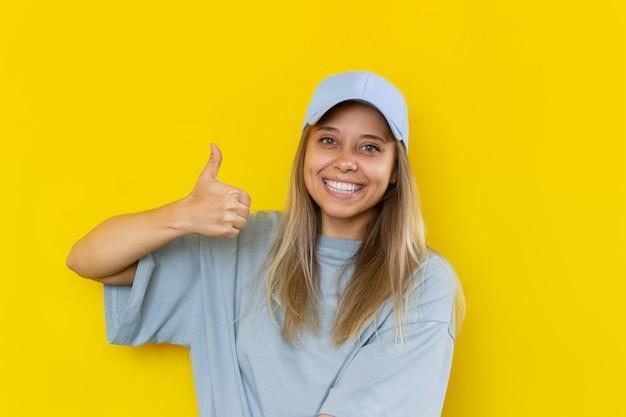 Молодая улыбающаяся блондинка показывает большой палец вверх жест рукой, изолированной на желтом фоне