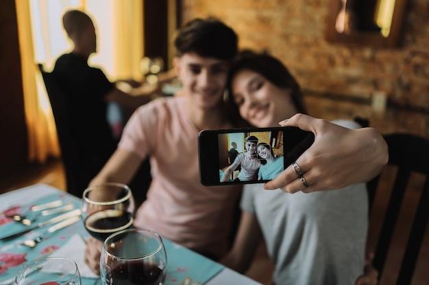 Молодая улыбающаяся пара сидит в ресторане и пьет вино - счастливая молодая пара делает селфи с помощью смартфона.