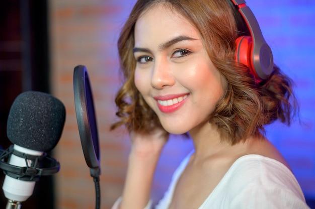 Молодая улыбающаяся певица в наушниках с микрофоном во время записи песни в музыкальной студии с яркими огнями.