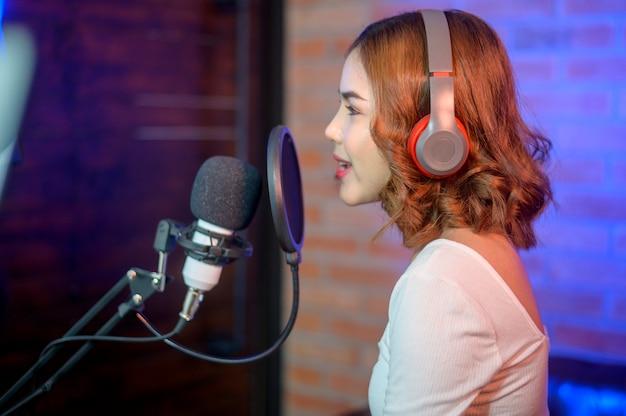 화려한 조명과 함께 음악 스튜디오에서 노래를 녹음하는 동안 마이크와 헤드폰을 착용하는 젊은 웃는 여성 가수.