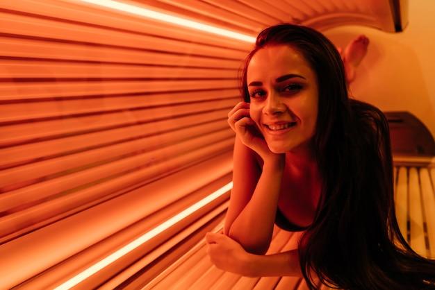 Молодая улыбающаяся девушка лежит в солярии под ультрафиолетовыми лучами, загорает, хочет загорелой кожи.