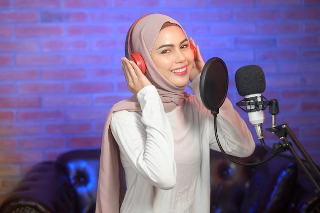 화려한 조명과 함께 음악 스튜디오에서 노래를 녹음하는 동안 마이크와 헤드폰을 착용하는 젊은 웃는 이슬람 여성 가수.