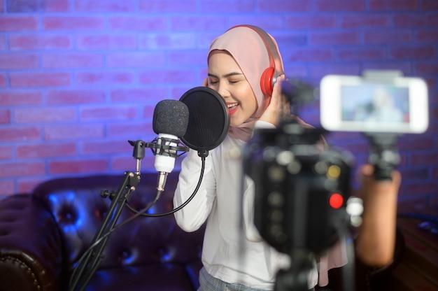 Молодая улыбающаяся мусульманская певица в наушниках с микрофоном во время записи песни в музыкальной студии с яркими огнями.