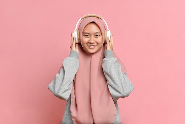 웃고 있는 어린 이슬람 소녀가 흰색 헤드폰으로 그녀가 좋아하는 음악을 듣고, 카메라, 즐거움, 음악 애호가, 분홍색 배경에 대해 봅니다.