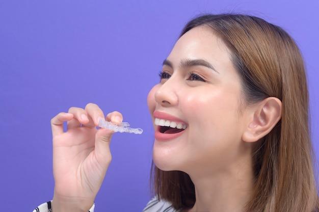 スタジオ、歯科医療、歯科矯正の概念でインビザラインブレースを保持している若い笑顔の女性。