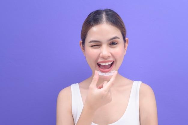 Молодая улыбающаяся женщина, держащая брекеты invisalign в студии, стоматологическом здравоохранении и ортодонтической концепции.