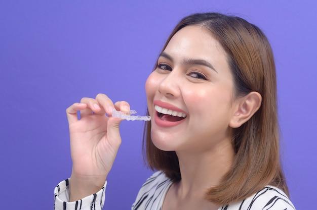 스튜디오, 치과 의료 및 교정 개념에서 invisalign 교정기를 들고 웃는 젊은 여성.