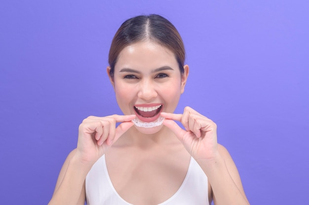 スタジオ、歯科医療、歯科矯正の概念でinvisalignブレースを保持している若い笑顔の女性