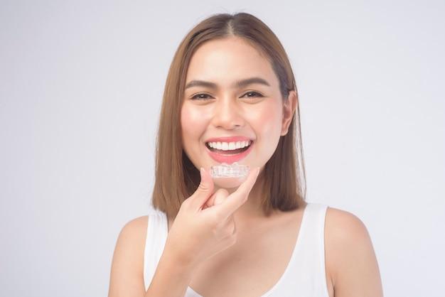 Молодая улыбающаяся женщина, держащая брекеты invisalign на белом, стоматологическом здравоохранении и ортодонтической концепции.