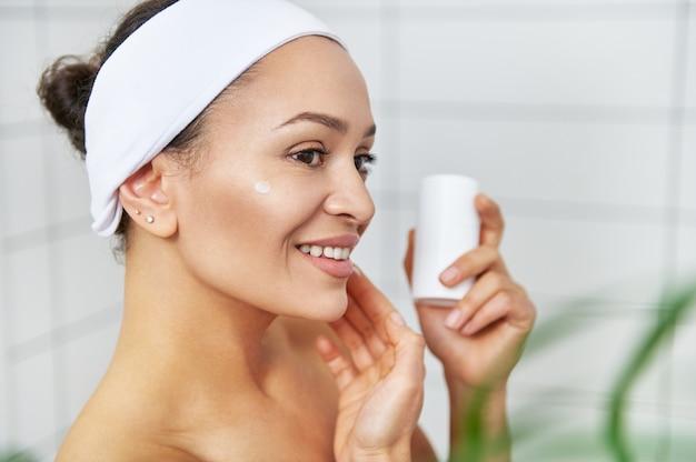 保湿クリームを持って顔に塗る笑顔の若い女性。スキンケアの朝のルーチン。