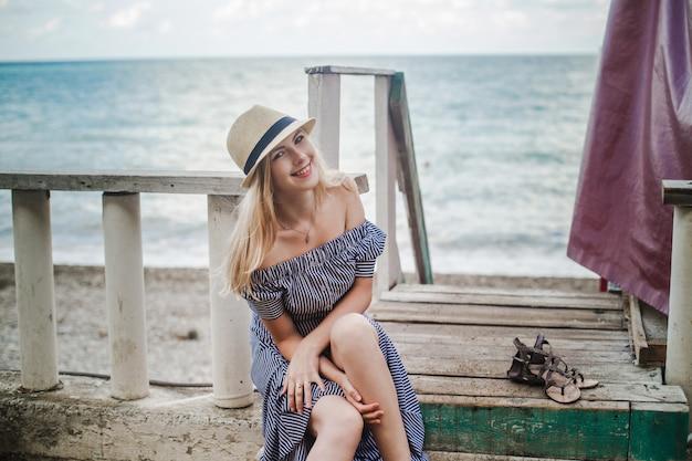 모자에 젊은 웃는 여자는 바다로 다리에 맨발로 앉아