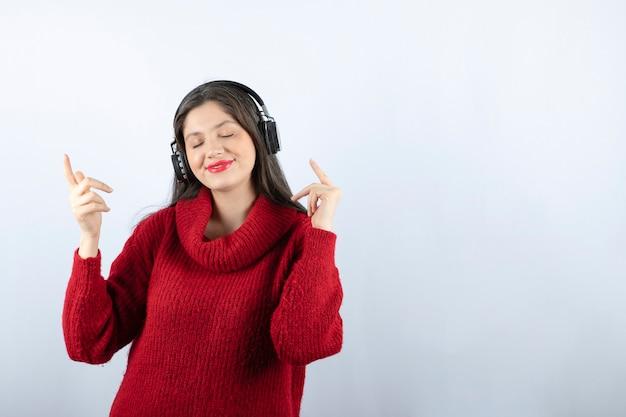Молодая улыбающаяся женщина в красном теплом свитере слушает музыку в наушниках