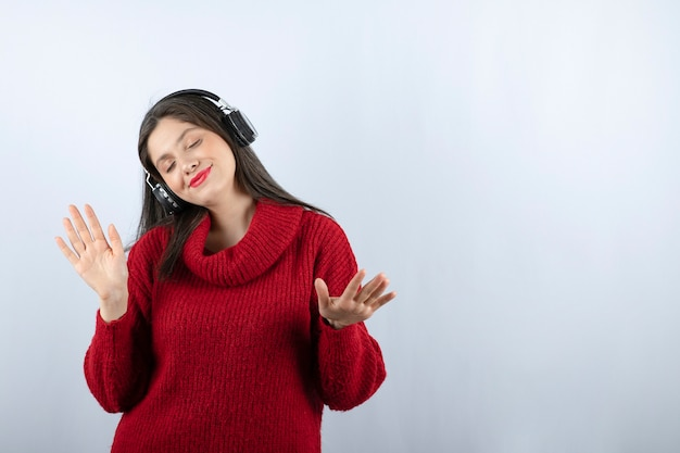 헤드폰에서 빨간색 따뜻한 스웨터 듣는 음악에 젊은 웃는 여자