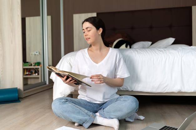 Молодая улыбающаяся женщина сидит, скрестив ноги, на полу и читает книгу. понятие образования и досуга.