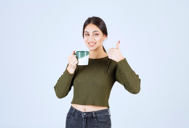 컵을 들고 엄지 손가락을 보여주는 젊은 웃는 여자 모델.