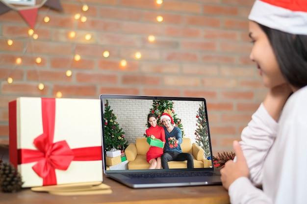 Молодая улыбающаяся женщина в красной шляпе санта-клауса делает видеозвонок в социальной сети с семьей и друзьями в день рождества.