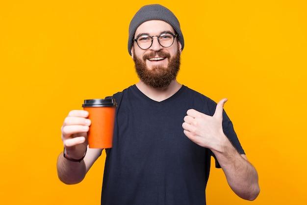 若い微笑む男は彼のコーヒーを楽しんでいて、親指を上げています