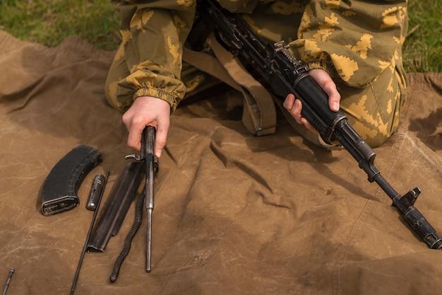 Молодой солдат в камуфляжной форме разбирает оружие. мужчина собирает автомат калашникова на траве на военных учениях.