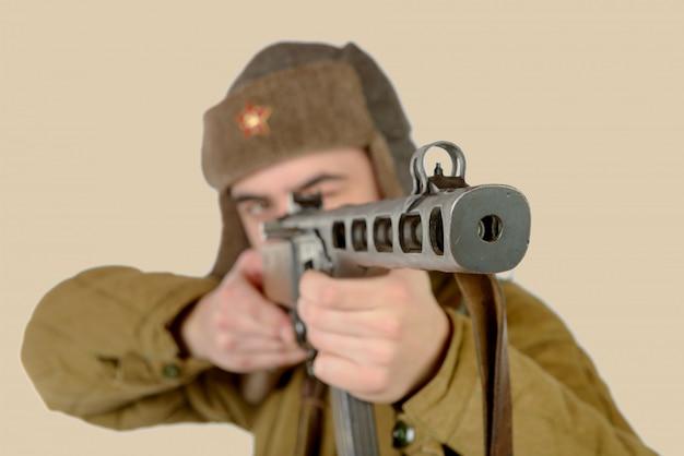 Молодой советский солдат стреляет из автомата