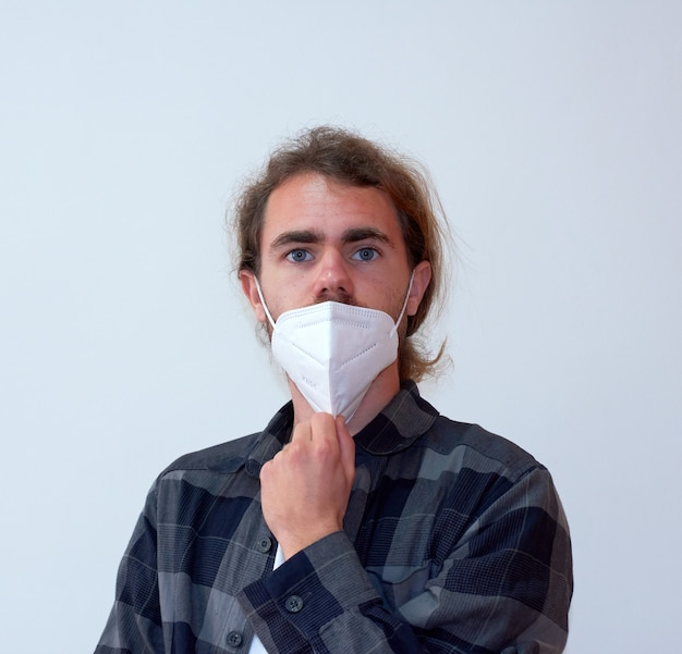 Молодой испанский мужчина снимает маску на белом фоне