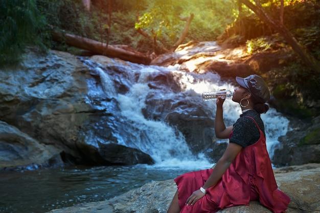 한 젊은 스페인 여성이 여름에 치앙마이의 매사 폭포 여행을 마치고 물을 마시고 휴식을 취합니다.