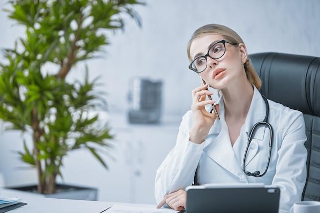 Молодой врач-специалист общается по мобильному телефону в своем кабинете