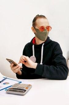 보호 마스크의 젊은 전문가가 금융 문서로 작업하고 스마트 폰을 들고 있습니다.