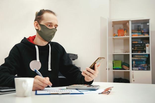 보호 마스크의 젊은 전문가가 컴퓨터에서 재무 문서로 작업합니다. 코로나 바이러스, 보호 마스크로 작업하십시오.