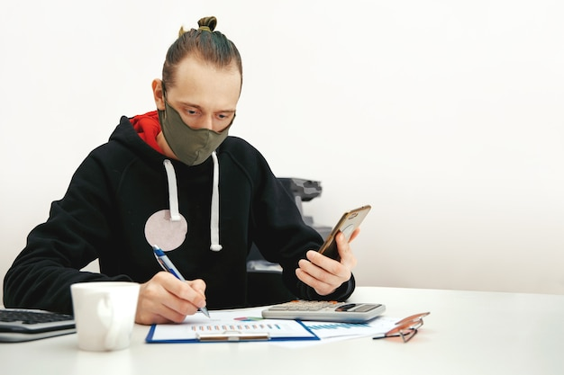 보호 마스크의 젊은 전문가가 컴퓨터에서 재무 문서로 작업합니다.