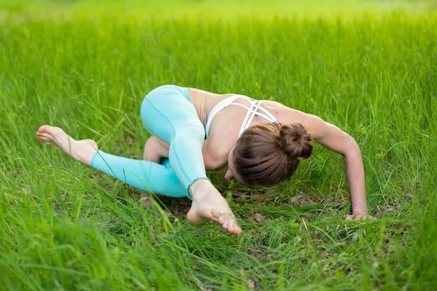 Молодая спортивная девушка занимается йогой в заброшенном зеленом летнем лесу.