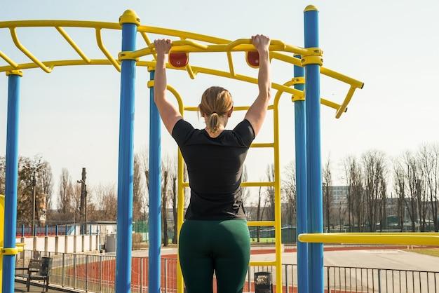 한 젊은 스포츠 소녀가 경기장의 가로 막대에 몸을 위로 당깁니다.