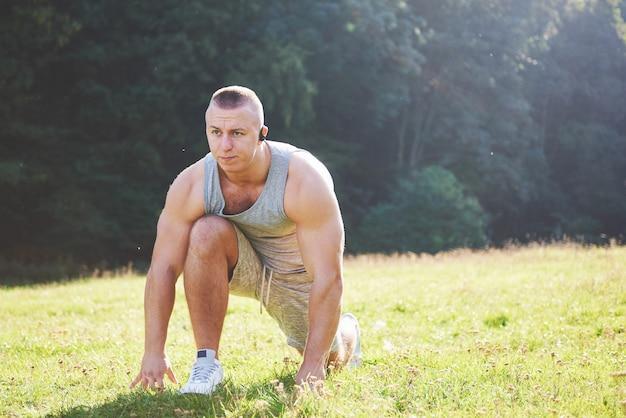 屋外での運動とフィットネスのトレーニングの準備をしている若いスポーツマン。