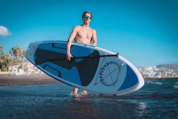Молодой спортсмен занимается серфингом на пляже под голубым небом