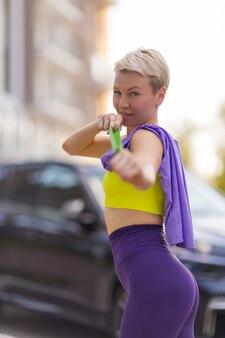 Молодая спортсменка с резинкой делает упражнения на открытом воздухе в городе