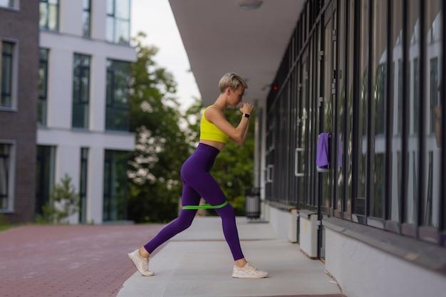 Молодая спортсменка с резинкой делает упражнения на открытом воздухе в городе.