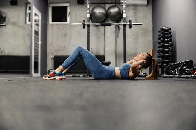 Молодая спортивная женщина тренируется и делает кранчи. ш. в позе велосипедного скручивания. на ней спортивная одежда в серой спортивной студии. тренажерный зал в помещении. спорт, любовь, образ жизни
