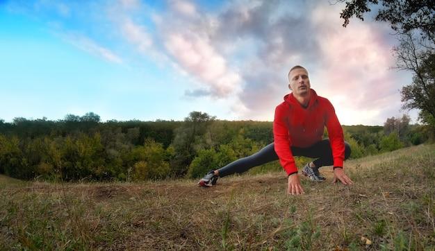 후드와 검은 색 스포츠 레깅스가있는 빨간 재킷을 입은 젊은 강한 운동 남자가 일몰 깊은 하늘이있는 녹색 숲에서 조깅하기 전에 다리로 워밍업을 수행합니다.