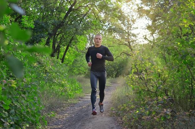 검은 색 스포츠 레깅스, 셔츠 및 운동화를 입은 젊은 강력한 조깅하는 사람이 녹색 봄 숲을 달립니다. 사진은 건강한 생활 방식을 보여줍니다.